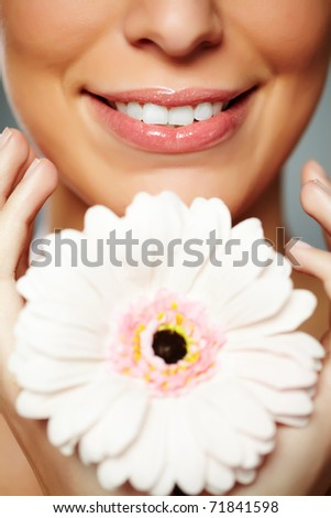 Fresh woman holding herbera and smiling - stock photo