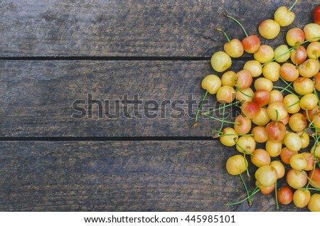 Fresh yellow cherry on a wooden background composition