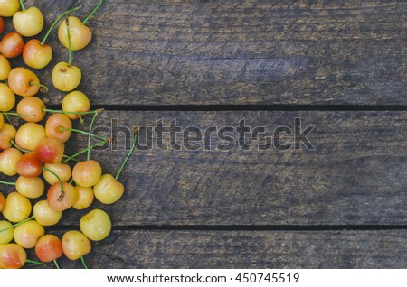 Fresh yellow cherry, wooden background, fresh cherry composition