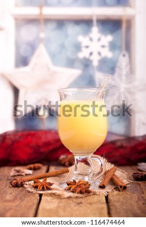 fresh yellow eggnog with cinnamon and anise seed for christmas on rustic wooden board with a blurred window stuffed with christmas decoration in background