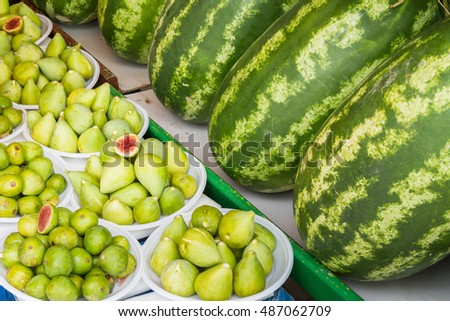 Fresh yellow green figs on white plates and watermelons.