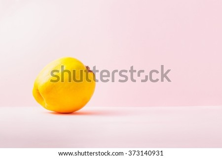 Fresh yellow quince over pink background, copy space - stock photo
