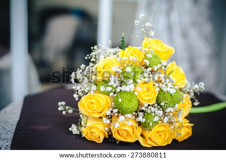 Fresh yellow roses with a checkered green ribbon on wooden table