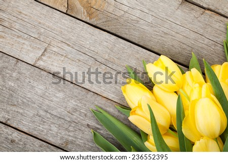 Fresh yellow tulips bouquet over wooden table background - stock photo