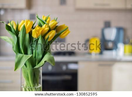 fresh yellow tulips on kitchen background - stock photo