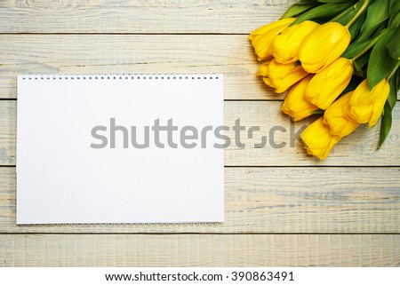 Fresh yellow tulips with easter greeting card on wooden background. Holiday background. Top view with copy space. - stock photo