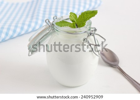 Fresh yogurt in a jar with mint leaves on a white table. - stock photo
