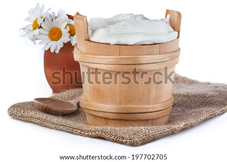 fresh yogurt in a wooden bowl on a linen canvas with white daisies behind - stock photo