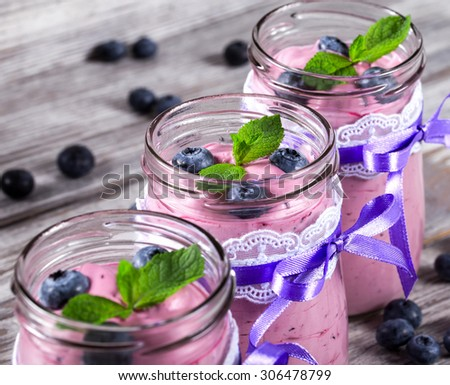 fresh yogurt with blueberries and mint in a glass jars, closeup, selective focus - stock photo
