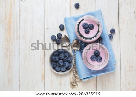 fresh yogurt with blueberries in glass jars - stock photo