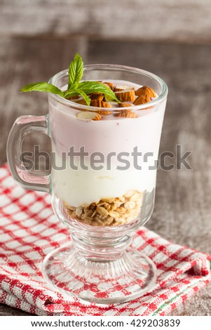 Fresh yogurt with granola and muesli, fresh berries and almonds nuts. Healthy morning breakfast of smoothie. - stock photo