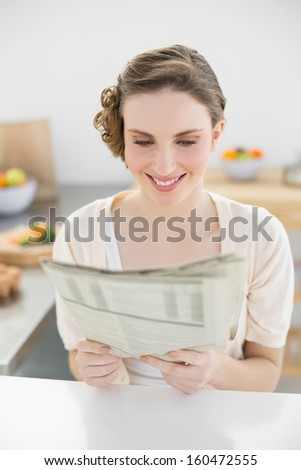 Fresh young woman reading newspaper sitting in her kitchen at home - stock photo