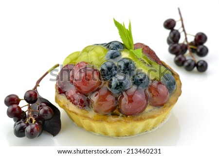 Fresh yummy tart made decorated with grape and berries on white background - stock photo