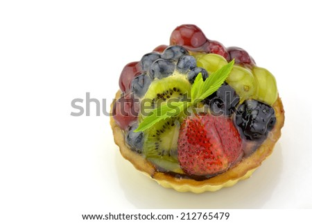 Fresh yummy tart made decorated with kiwi slices, berries and mint leaves on white background - stock photo