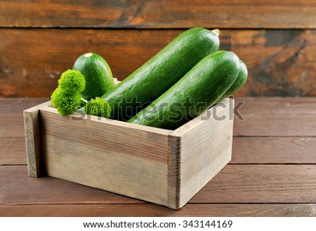 Fresh zucchini in box on wooden background - stock photo