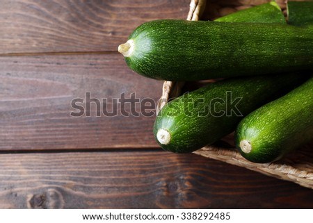 Fresh zucchini in wicker basket on wooden background - stock photo