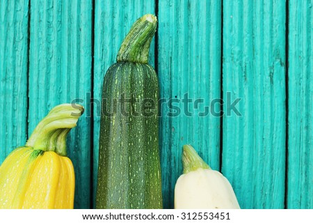 fresh zucchini on turquoise background - stock photo