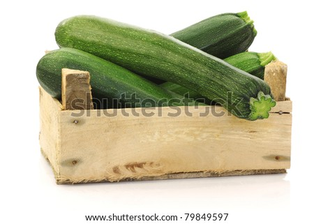 fresh zucchini's (Cucurbita pepo) in a wooden box on a white background - stock photo