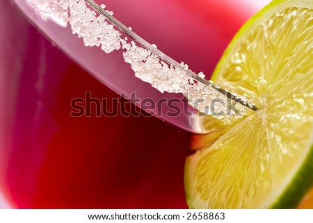 Freshening fruit cocktail with liquor decorated by segments of lime - stock photo