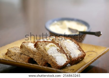 Freshly baked and sliced banana bread with butter - stock photo