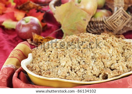 Freshly baked apple crisp with fresh apples and autumn leaves in the background. Shallow depth of field with selective focus on the foreground. - stock photo