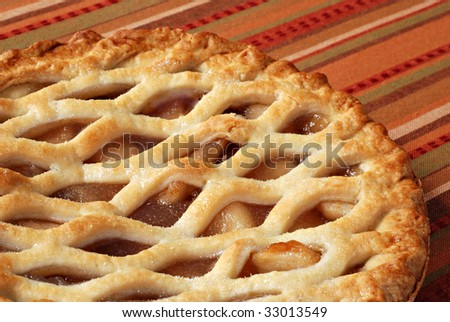 Freshly baked apple pie on colorful tablecloth.  Macro with shallow dof. - stock photo
