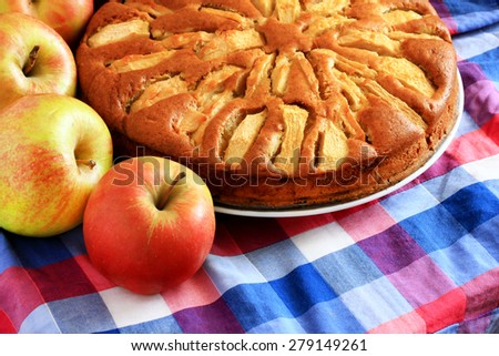 Freshly baked apple pie with apples in the background - stock photo