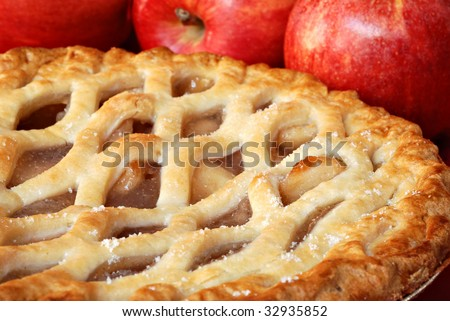Freshly baked apple pie with apples in the background.  Macro with shallow dof. - stock photo