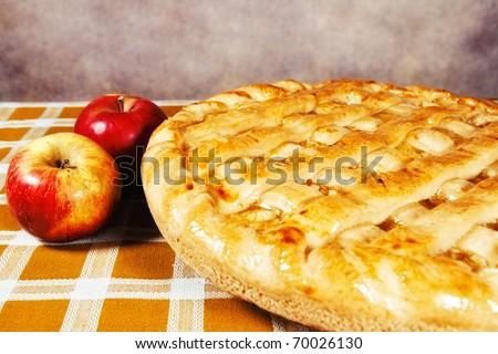 Freshly baked apple pie with apples on the side (shallow dof) - stock photo