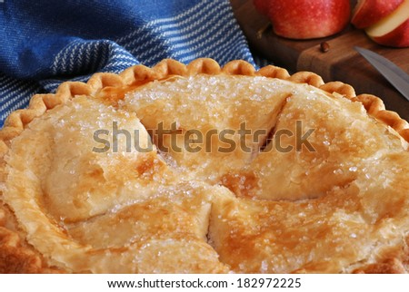 Freshly baked apple pie with sliced apple and knife on wooden cutting board in background.  Rustic still life with natural, directional lighting and shallow dof. - stock photo