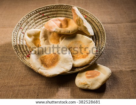 Freshly baked arabic bread. A basket full of fresh Arabic flat bread. Middle eastern food photography. - stock photo