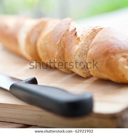 Freshly baked baguette sliced on wooden board - stock photo