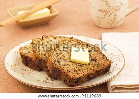 Freshly baked banana bread slices with butter and mug of tea in horizontal format - stock photo