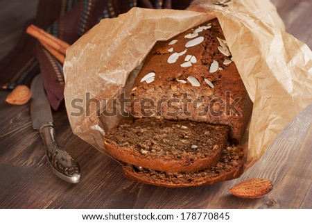 Freshly baked banana bread with almond cinnamon and in baking paper on the wooden - stock photo