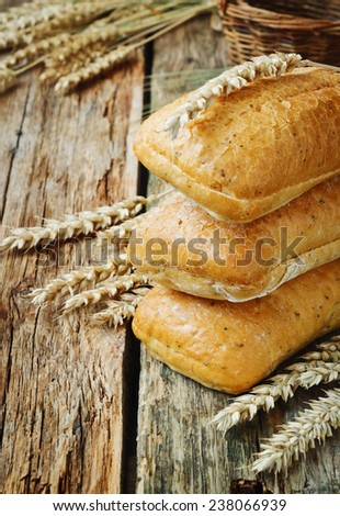 freshly baked bread and ears of wheat on the old wooden background. selective focus - stock photo