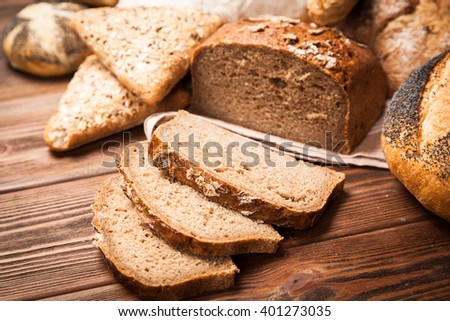 Freshly baked bread assortment on wooden surface - stock photo