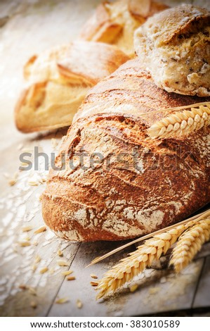 Freshly baked bread in rustic setting - stock photo