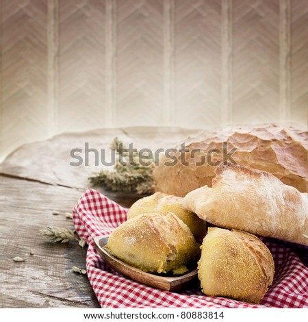 Freshly baked bread variety on wooden background - stock photo