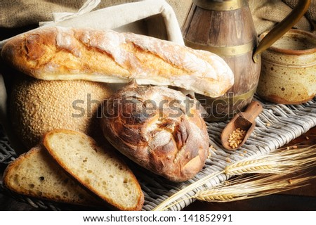 Freshly baked bread with jug in countryside setting - stock photo