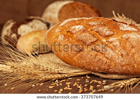 Freshly baked breads with grains and ears . Shallow depth of field. - stock photo