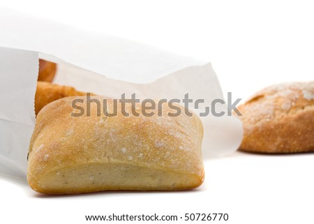 Freshly baked buns in paper bag over white background - stock photo