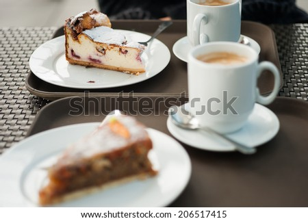 Freshly baked cheese cake with a slice of carrot cake in the foreground - stock photo