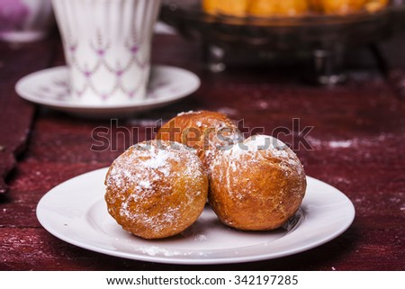 Freshly baked cheese donuts with powdered sugar on a parchment paper - stock photo