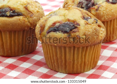 freshly baked cherry muffins on a red and white checkered table cloth - stock photo