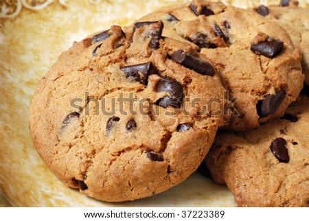 Freshly baked chocolate chip cookies on decorative plate.  Macro with shallow dof. - stock photo