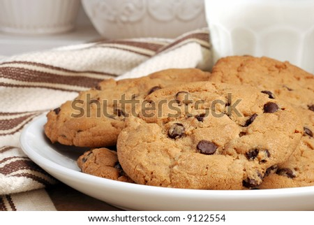 Freshly baked chocolate chip cookies with glass of milk.  Ceramic cookie jars in soft focus in the background.  Close-up with shallow dof. - stock photo