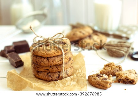 Freshly baked chocolate chip cookies with glass of milk on rustic wooden table. The toning.