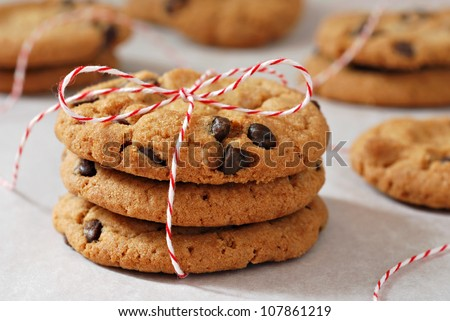 Freshly baked chocolate chips cookies tied with festive baker's twine and stacked on parchment paper.  Macro with extremely shallow dof. - stock photo
