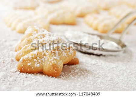 Freshly baked Christmas tree cookies sprinkled with confectioners sugar on parchment paper.  Stainless steel sugar duster in soft focus in background.  Macro with extremely shallow dof. - stock photo