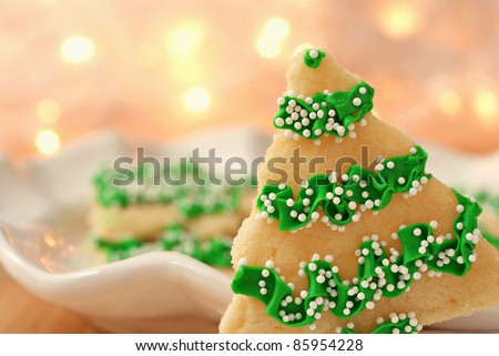 Freshly baked christmas tree cookies with defocused golden lights in background.  Macro with extremely shallow dof and copy space. - stock photo